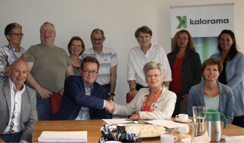 Fieke van Deutekom (bestuurder van Kalorama) en Frank van Rennes, (eigenaar Van Rennes Groep) schudden elkaar de hand na de ondertekening. Collega's en bewoners zijn hiervan getuigen.