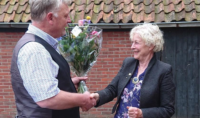 Christine Stigter ontvangt bloemen en het bijbehorende jubileuminsigne uit handen van fractievoorzitter Ubel Zuiderveld.