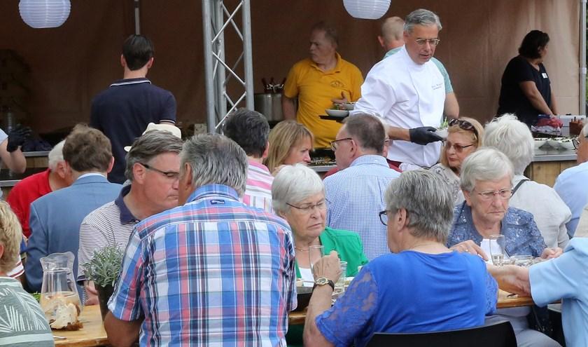 Niet alleen kookte burgemeester Brenninkmeijer tijdens het dorpsdiner in 2018, hij stak ook nog een handje toe bij het uitserveren. Foto: Theo van Sambeek.
