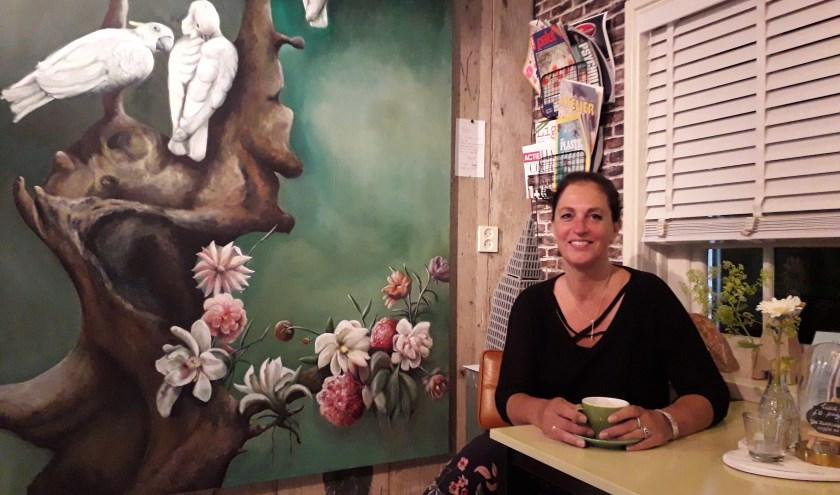 Petra Keyl in 'De Zwaluw - Koffie en zo'. Het schilderij met de witte kaketoes maakte ze zelf. (Foto Margaretha Coornstra)