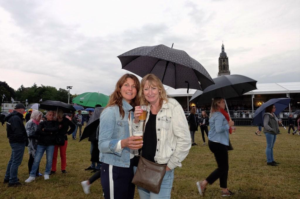 Ondanks de regen laten Margrietha en Marina uit Rhenen zich het biertje goed smaken.(Foto: Max Timons)   © Persgroep