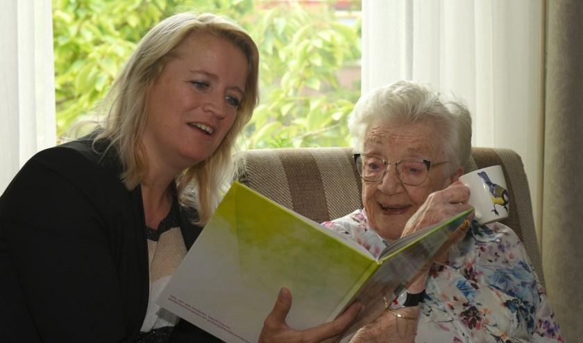 De 101-jarige mevrouw Bekkers en wethouder Patricia van Aken bekijken het fotoboek. (Foto: Marius Schinkel)