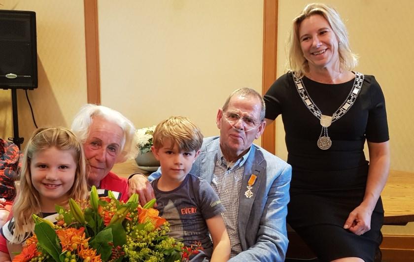 Jan en Betsy Kampherbeek met hun kleinkinderen na het uitreiken van de koninklijke onderscheiding door burgemeester Koops.