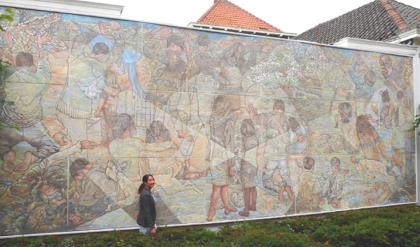 Marjon Hoogendijk voor haar kunstwerk van 4 bij 12 meter dat ze onlangs restaureerde. (Foto: Bart van der Linden)