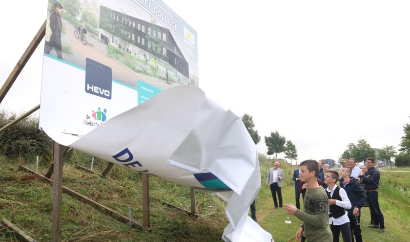 Na wat trekken en duwen gaf het grote zeildoek zich toch gewonnen en werd de afbeelding van de nieuwe school zichtbaar. (foto: Conno Bochoven)