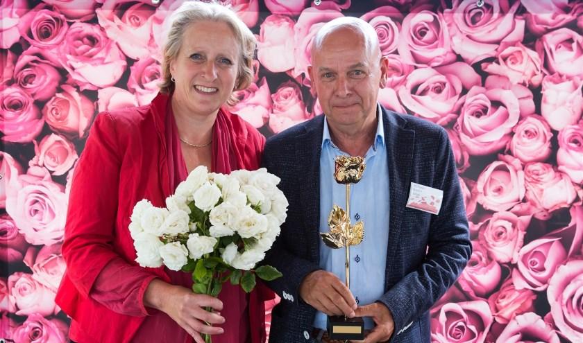 Rozenkweker Martin Vissers krijgt de Gouden Roos uit handen van stadsdeeldirecteur Mendy van Veen.