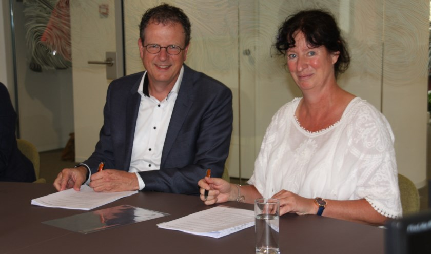 Alfred van den Bosch (links) namens Wooncompas en Sonja Krau (rechts) namens IJsselmonde-Oost ondertekenen het contract.
