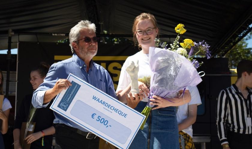 Winnares Louise van Beuzekom ontvangt de Antoine Gerrits Award Trofee en de prijs uit handen van Antoine Gerrits, naamgever van de Award en een van de oprichters van de Vereniging CultuurprofielScholen.