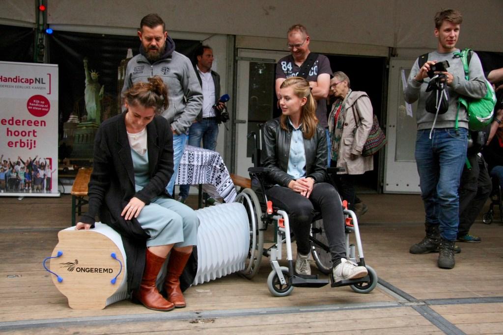 Ontwerpers van Ongeremd demonstreren de festivalrolstoel met zitbankje uit het wiel.   © Persgroep