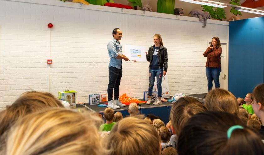 Elisa Kruithof van de St. Bernardusschool heeft een project bedacht voor kinderen in Laos. Keo, de partner van juf Simone, ontving de cheque.