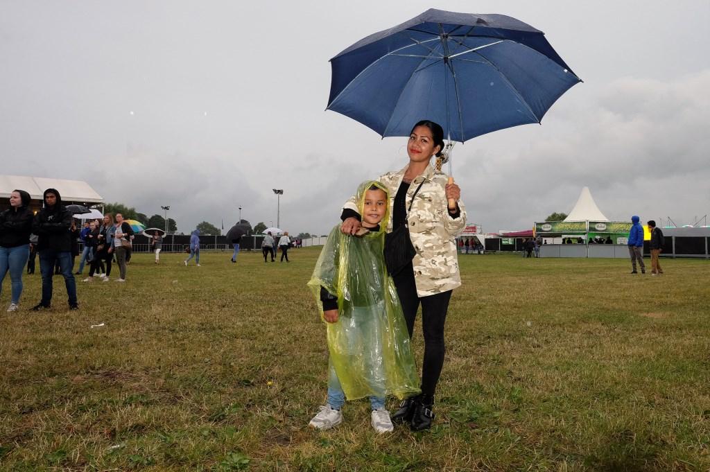 moeder en zoon uit opheusden trotseren de regen. (Foto: Max Timons)   © Persgroep