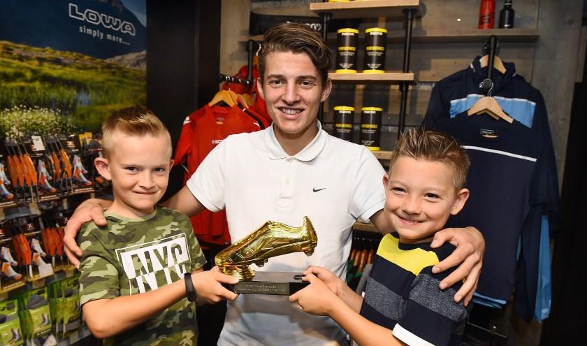 Alexander Megens (midden) krijgt de Gouden Schoen van Fabian (links) en Sem.