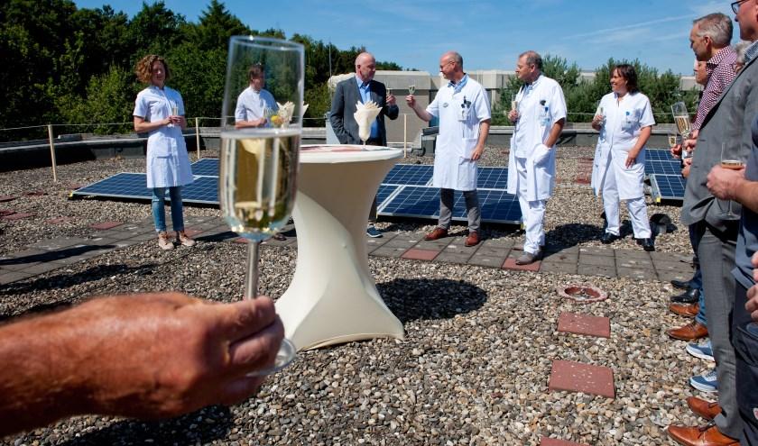 Specialisten en bestuur CWZ proosten, op het dak, op de aanleg van ruim 1000 zonnepanelen.