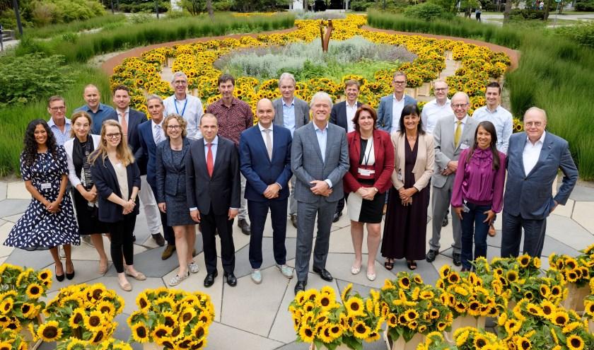 Een aantal belanghebbenden m.b.t. de samenwerking poseert tussen de zonnebloemen. FOTO: Bart van Overbeeke Fotografie.