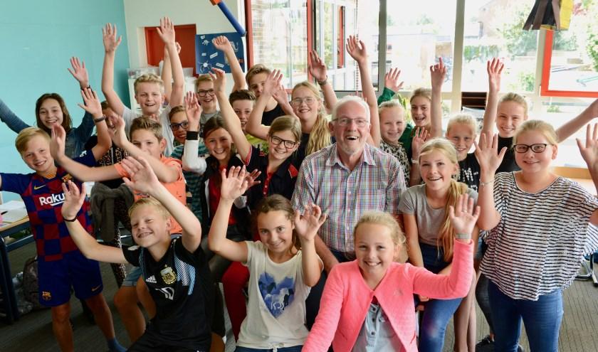 Voor het vertrek van school eerst nog met meester Dick Trappenburg temidden van de kinderen van groep 7 en 8 op De Kievitsheuvel op de foto.