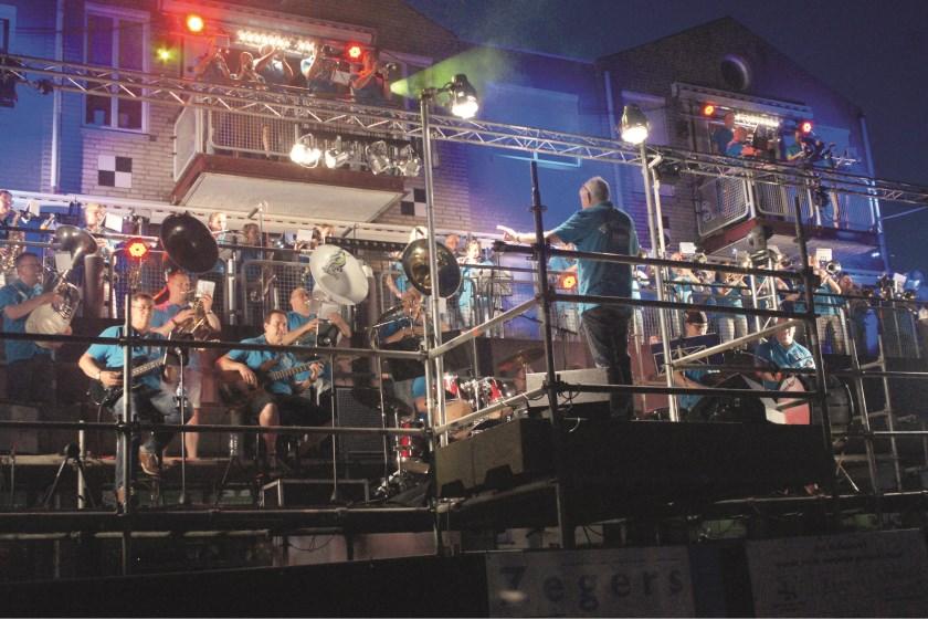 Dirigent en muzieksamensteller Louis Peters geeft het ritme aan tijdens het Balkoncert zaterdag op het Dorpsplein.