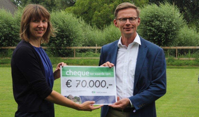 Directeur Belle van den Berg van Museum HW (l) pakte met genoegen de mooie cheque van wethouder Harry van Waveren aan. (foto: gem. Hoeksche Waard)