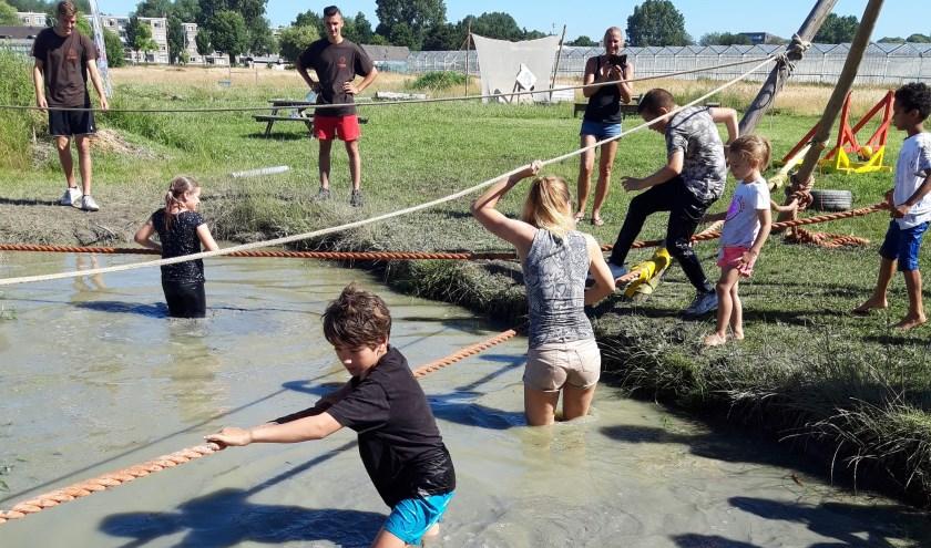 De kinderen steken de modderpoel over via een touwbrug.