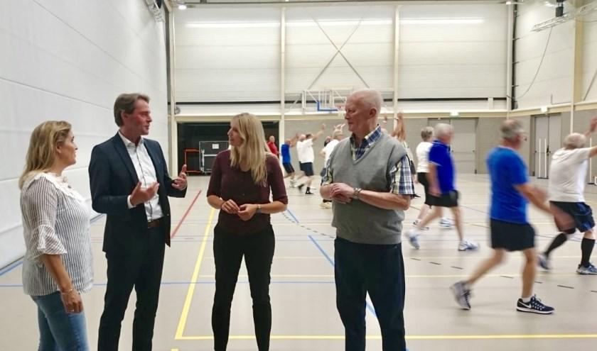 Wethouder Paul Boogaard (tweede van links) in gesprek met bestuursleden. Op de achtergrond de sportende leden.