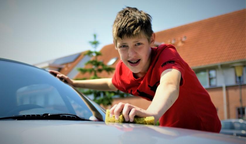 Jullian probeert zijn zakgeld aan te vullen door in de zomervakantie auto's te wassen. Foto: Robbert Roos