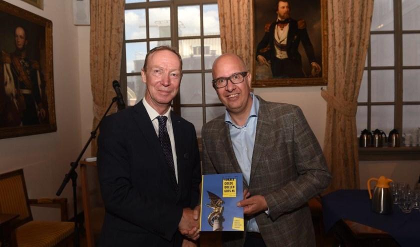 Jan de Rond van Mooi zo Goed Zo (l) en burgemeester Jack Mikkers met het eerste exemplaar van de goededoelengids. Foto: Henk van Esch