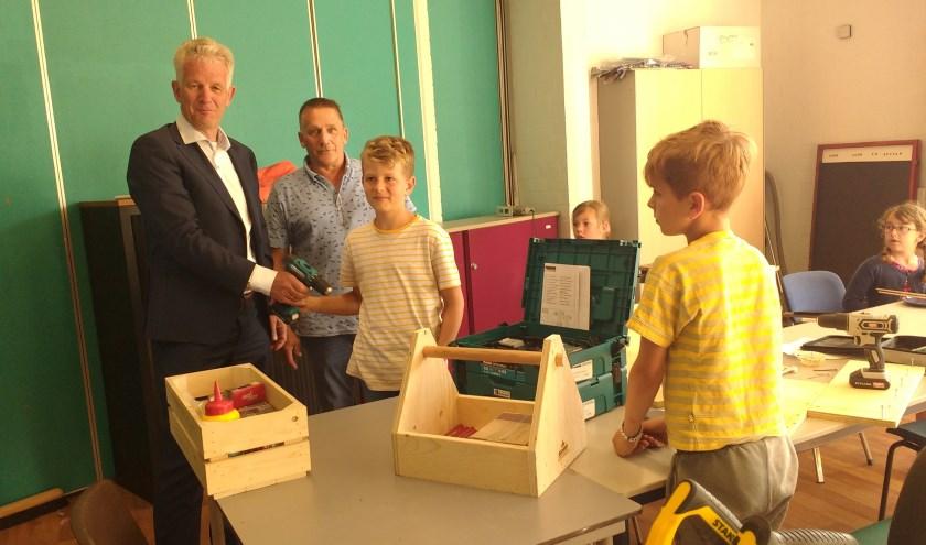 Hans Boogert overhandigt materialen en gereedschap aan Leen Verloo en kinderen van de Timmerclub. FOTO: Petra Ruitenbeek