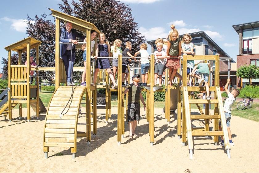 Kinderen uit de buurt poseren samen met wethouder Johannes Goossen op het nieuwe speeltoestel aan de Hunneschansallee.