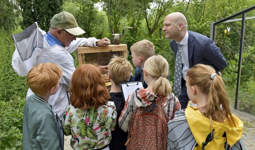 Geintereesseerd luistert wethouder Armand van de Laar in het Wilhelminapark naar de uitleg van de imker.