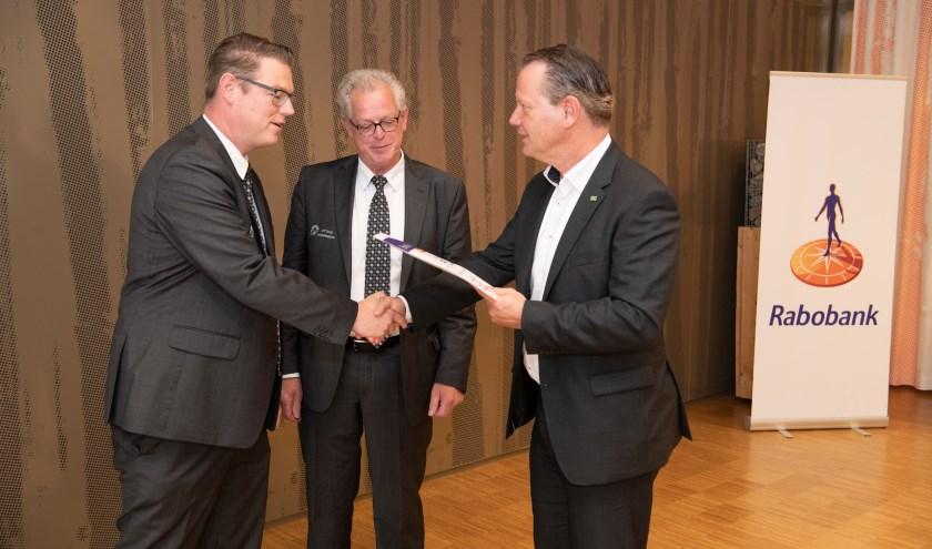 Steven Enneman reikt Niels Berendsen en Sjon Slütter van het Ettens Mannenkoor de cheque van €2.500 uit