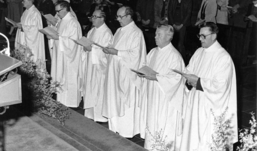 We zien zeven priesters op een rij waarvan we de middelste herkennen als Pastor van der Sanden.