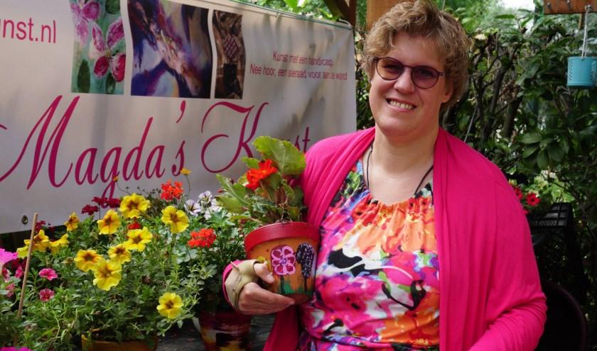 Magda Strijbosch met de bloempotten die ze verkoopt ten bate van Stichting De Zonnebloem. FOTO: Ellis Plokker