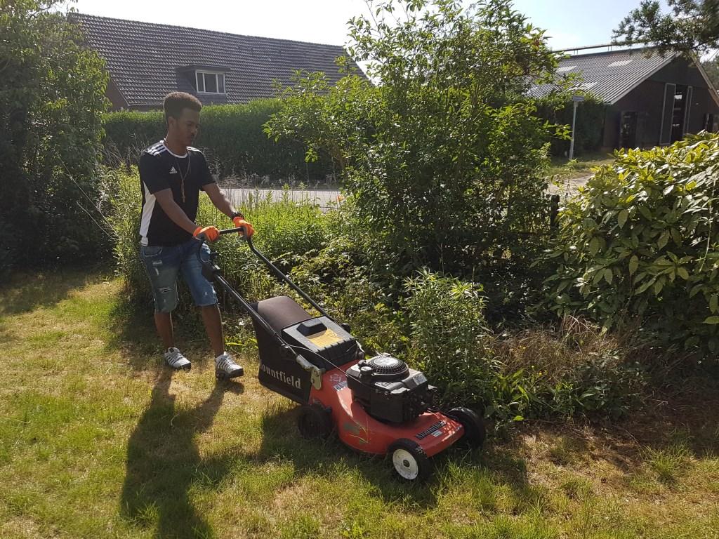 Een van de studenten maait het gras in de voortuin. Foto: Present Winterswijk © Persgroep