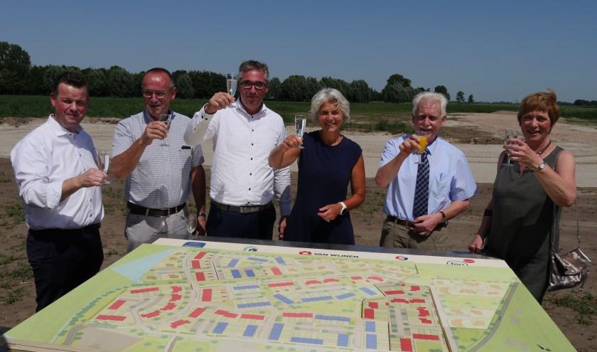 De wethouders Lyda Sneevliet en Henk Wessels proosten met vertegenwoordigers van andere partijen op de komst van de nieuwbouwwoningen. (Foto: gemeente Elburg)