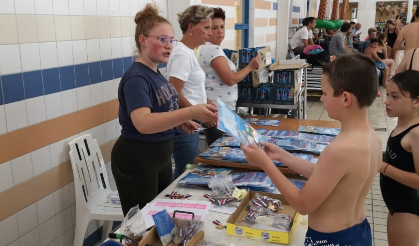 Kinderen nemen tijdens de zwemvierdaagse spulletjes in ontvangst. FOTO Carolien van Winsen