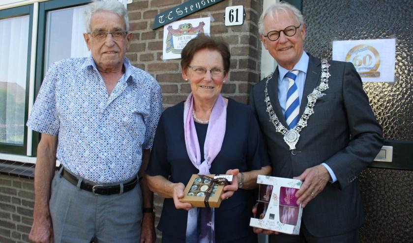 Burgemeester Lokker verraste het echtpaar thuis met chocolaatjes  en Leerdamse glazen. Foto: Mieneke Lever-van Dieren