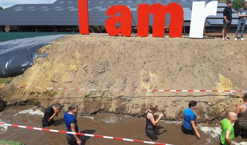 Deelnemers ploeteren door de modder