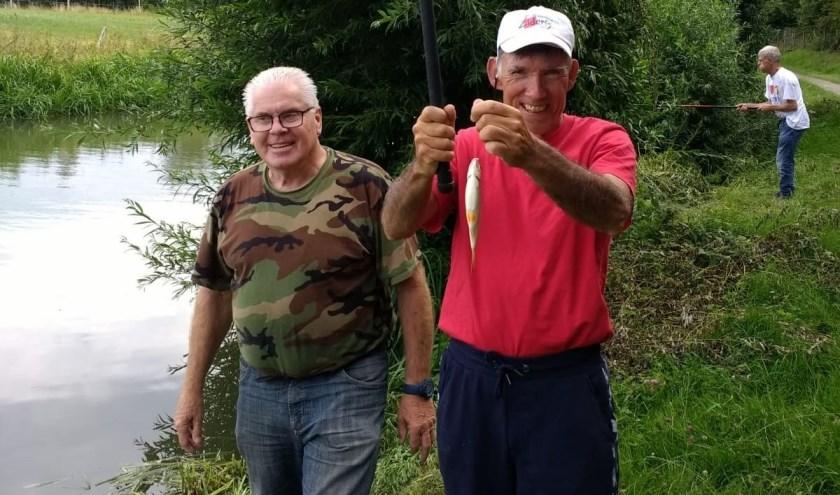 Leo Lieuwen (links) een van de vrijwillige leden van De Voorn, met een bewoner van Zideris die een vis aan de haak heeft. (Foto: Henk Jansen)