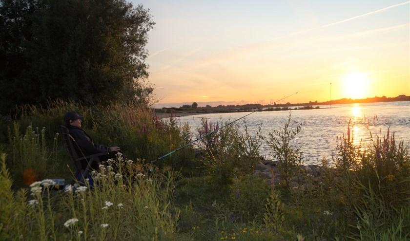 Visser Rein geniet van de rust en de ondergaande zon tijdens het vissen.