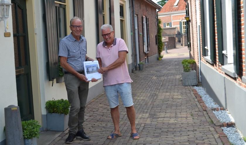 Jos Wessels (links) met Arjan Twigt en het boek 'Bezield Erfgoed' in een Bredevoorts straatje. Foto: Karin Stronks