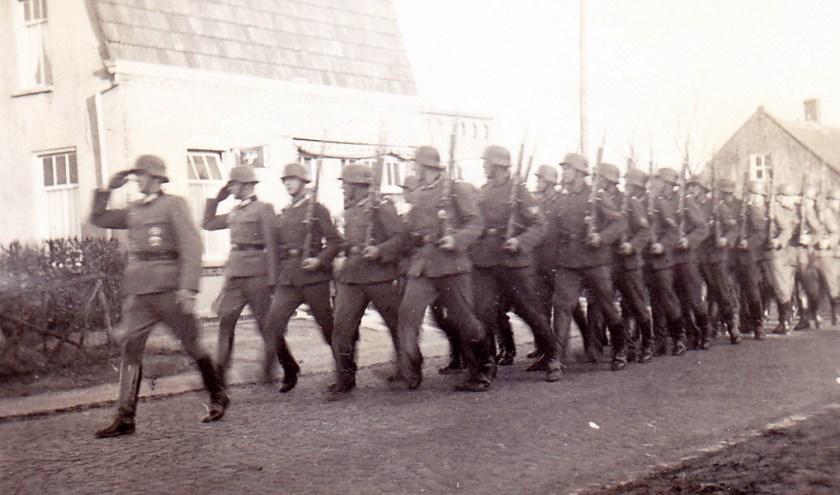 Duitse militairen marcheren binnen via de Dorpstraat. FOTO: Picasa.