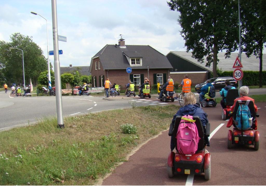 Bij de oversteekplaatsen wordt altijd voor de nodige beveiliging gezorgd voor de scootmobielberijders. Foto: Cees van Cuijlenburg © Persgroep