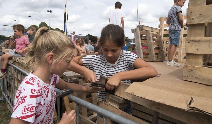 Veere (links) en Mara zijn geconcentreerd bezig om een mooie hut te bouwen voor het kinderdorp in Elst (foto: Ellen Koelewijn)