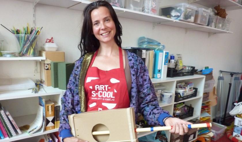 Sara met een gitaar van een doos, een pvc-pijp en elastiek. Kinderen kunnen deze zomer zelf instrumenten maken.