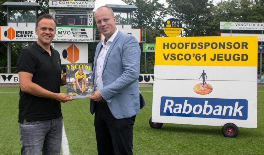 Financieel Adviseur van de Rabobank Noord Veluwe Peter Krist ontvangt de nieuwe presentatiegids uit handen van Colin Pelleboer. (Foto: Dries van Dijk)