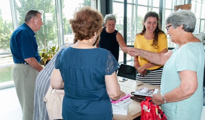 Fotografe Milene van Arendonk (tweede van rechts) wordt door lezers gefeliciteerd met haar boek over de Haagse koffietent.