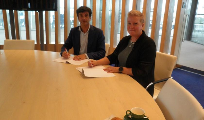 Burgemeester Pieter van de Stadt en Karin Krijnen (NL Confidential) ondertekenen het convenant Meld Misdaad Anoniem. Foto: Kees van Rongen