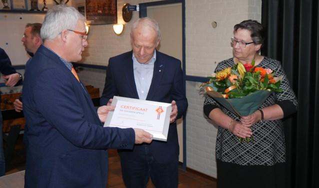 Henk ontvangt het certificaat behorende bij de gouden speld uit handen van Toon Kerkhof, met naast hem zijn vrouw Marieke   | Fotonummer: 23e2da