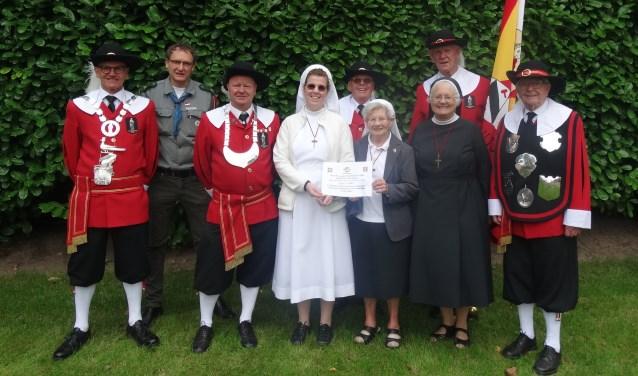 Aanbieding van een cheque aan de zusters van het Kostbaar Bloed Aarle-Rixtel. Op de foto staat ook de nieuwe koning Mario Van den Elsen  | Fotonummer: af79e6