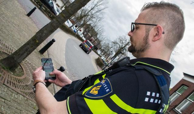 Wijkagent van Aarle-Rixtel, Roel Timmermans, bezig met de app van Nextdoor  | Fotonummer: 46b6d4