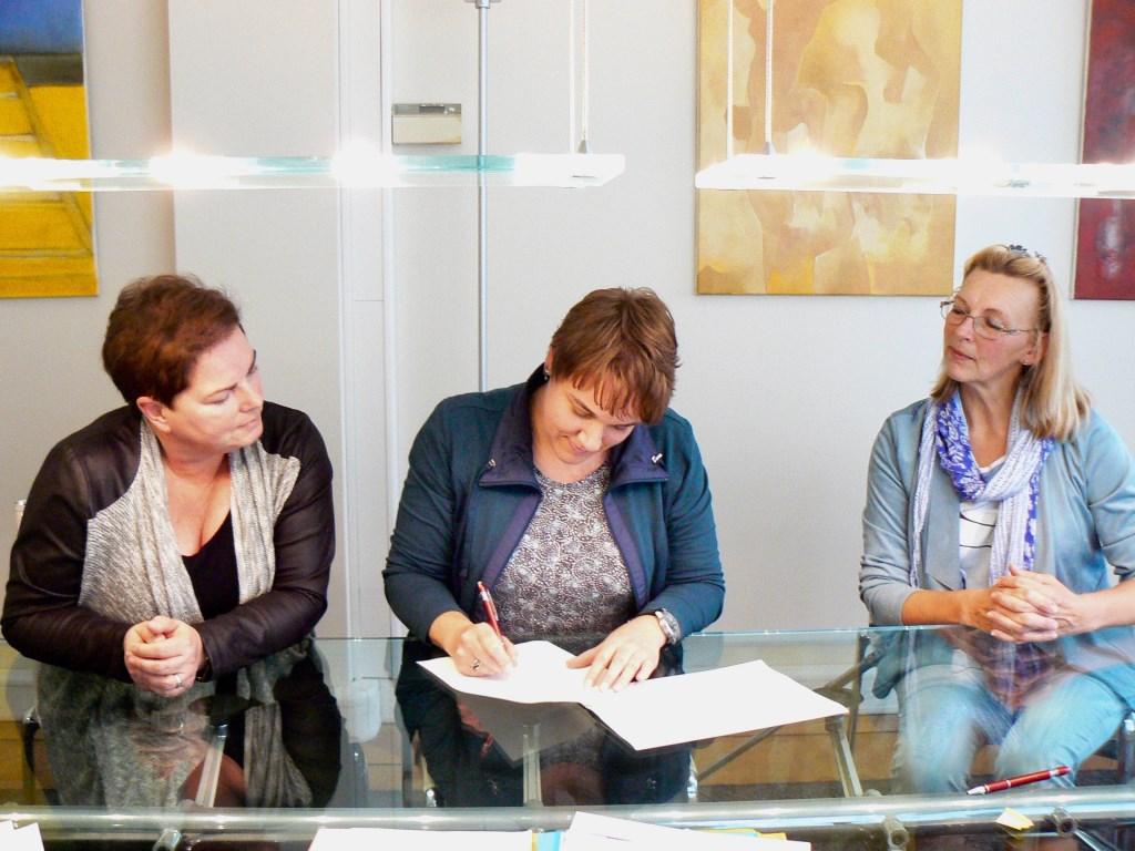 Voorzitter Brenda Filippo tekent de oprichtingsakte. Met aan weerszijden penningmeester Wies Hazenoot en secretaris Noortje Bloemzaad. | Foto: PR Foto: PR © uitgeverij Verhagen